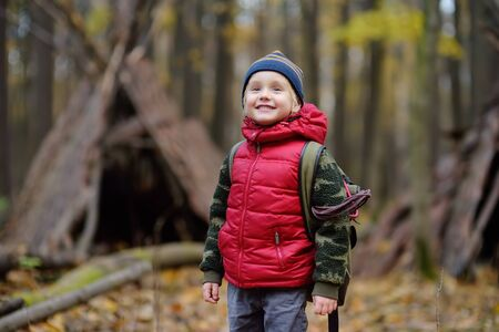 Little boy scout during hiking in autumn forest. Teepee hut on background.Concepts of adventure, scouting and hiking tourism for kids.