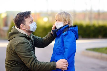 Mature man wearing a protective mask puts a face mask on a his son in airport, supermarket or other public place. Safety during COVID-19 outbreak. Epidemic of virus covid. Stock Photo