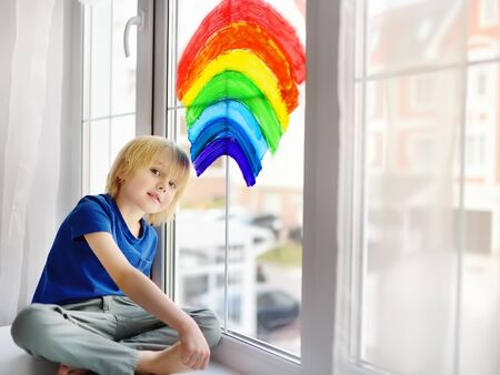 Little boy sitting at window with drawing rainbow while coronavirus quarantine. Rainbow sign is symbol of hope, means that everything will be OK. Stay at home for lockdown coronavirus. Banque d'images