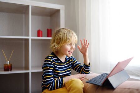 Little boy is meeting and talking in video chat while coronavirus pandemic. Stay at home during quarantine.Communication with relatives and friends online. Keeping social distance.