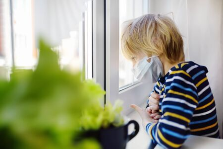 Sed little boy looking into window during coronavirus pandemic. Child boring without communication and walking. Stay at home while quarantine. Keeping social distance.