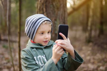 Little boy making photo or video call with smartphone during walking in the forest in spring or autumn. Modern technology.