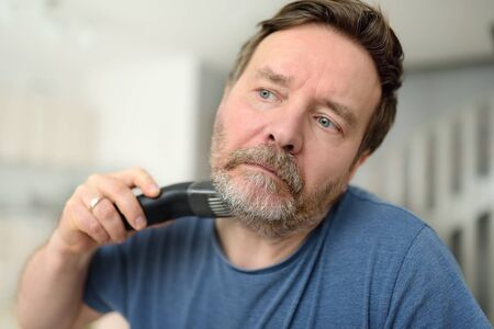 Mature man is shaving off his beard with electric razor at home during quarantine. Handsome bearded man trimming his beard with a trimmer at home while barbershops closed. Standard-Bild