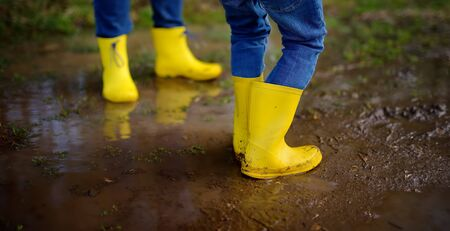 Mischievous preschooler child and adult wearing yellow rubber rain boots jumping in large wet mud puddle. Person playing and having fun. Outdoors games in spring.
