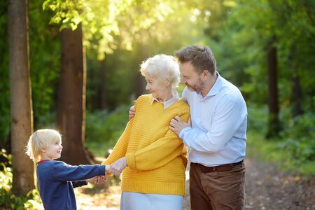 Beautiful eldery woman and her adult son, and her little grandson tenderly embracing together in park. Three generations of family