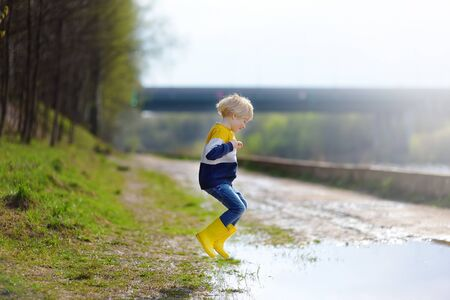 Mischievous preschooler child wearing yellow rubber rain boots jumping in large wet mud puddle after rain. Kid playing and having fun in sunny spring day. Outdoors games for children.