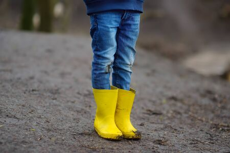 Mischievous preschooler child wearing yellow rain boots walking by muddy road. Kid playing and having fun. Outdoors games for children.