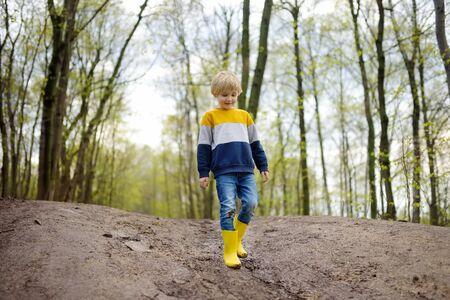 Mischievous preschooler child wearing yellow rain boots walking by muddy road. Kid playing and having fun. Outdoors games for children. Stok Fotoğraf