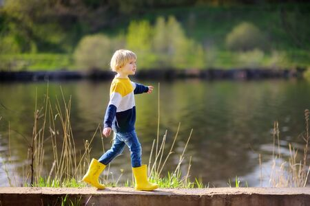 Preschooler child wearing yellow rain boots walking near river after rain. Kid playing and having fun in sunny spring or summer day. Outdoors games for children.