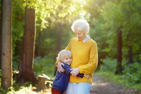 Loving grandson tenderly embracing his joyful elderly grandmother during walking at summer park. Two generations of family. Stok Fotoğraf