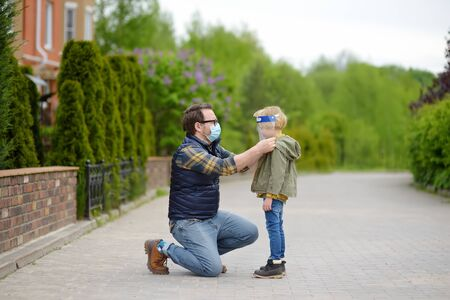 Man in facemask putting face shield on child on street or park. Safety during COVID-19 outbreak. Lifting virus lockdown. Social distancing and face mask - security measures when exiting quarantine.