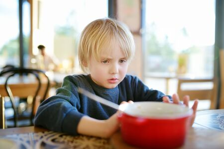 Little boy sitting the table in cafe or restaurant and doesn't want to eat. Healthy food. Kids diet. Poor appetite. Stop gesture. Do not force the child to eat.