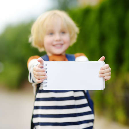 Happy little boy with backpack going to school. Child holding with hands empty white blank card for copy space and free text. Space for your advertising or information.