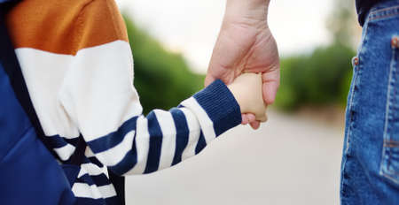 Little boy with his father going to school after summer break. Close-up photo of child and parent hands. Education for little kids. Back to school concept.