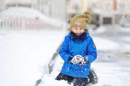 Little boy having fun playing with fresh snow during snowfall. Kid dressed in a warm clothes, hat, hand gloves and scarf. Active leisure outdoors for child on nature in snowy winter day. Stock Photo