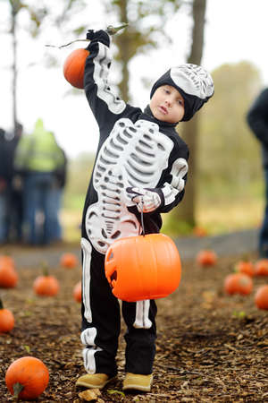 Little boy in scary skeleton costume at halloween celebrations party in forest. Halloween - traditional american holiday. Kid ready for trick or treat on Halloween night