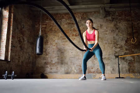 Young woman exercising with battle ropes at the gym. Strong female athlete doing crossfit workout with battle rope. Regular sports boosts immune system and promote good health and resistance to diseases. Healthy lifestyle 免版税图像