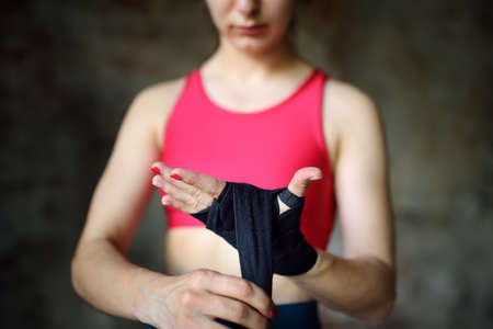 Young female boxer preparing for boxing fight. Athletic woman wearing strap on wrist before boxing practice in gym. Regular sports boosts immune system and promote good health and resistance to diseases