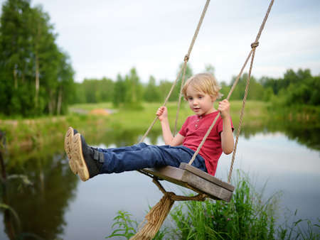 Little boy having fun on a swing hanging on big tree near pond or river in the forest in summer day. Active leisure outdoors for child on nature in summer day.