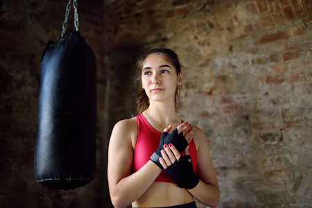 Young woman ready for hits punching bag during a boxing training. Female boxer doing fitness. Regular sports boosts immune system and promote good health and resistance to diseases. Healthy lifestyle
