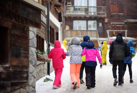 Group of teenager tourists walking on street of mountain resort town in Switzerland, Europe. Winter vacation concept in Alps. Ski resort.