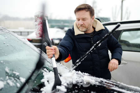 A mature man cleans his car with a brush after a snowfall. Snowdrift after a snowstorm on the hood of the automobile. Difficult transport situation on the roads in the city after a snow storm