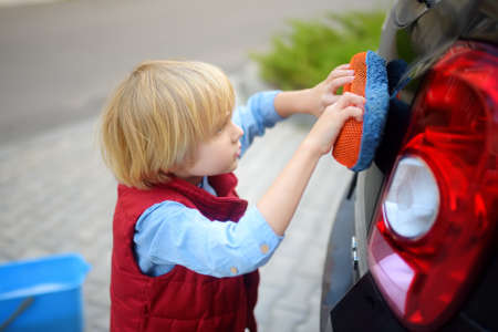 Preschooler boy helping his father washing family car. Little dad helper. Family with children spends time together in the backyard
