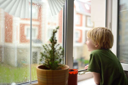 Little boy watching the rain outside at opened window. Bad weather - wind and downpour. Child boring and waiting of rainfall finish. Inquisitive kid explore nature.