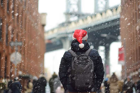 Middle aged man tourist in a Santa Claus hat is walking during a snowfall near Manhattan Bridge in New York on a snowy Christmas Eve. Winter Xmas holidays in NY. New Year vacations in NYC.