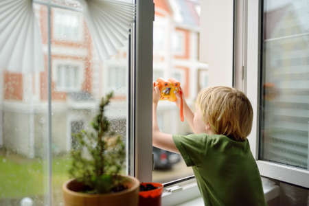 Little boy watching the rain outside at opened window and taking photo. Bad weather - wind and downpour. Child boring and waiting of rainfall finish. Inquisitive kid explore nature.