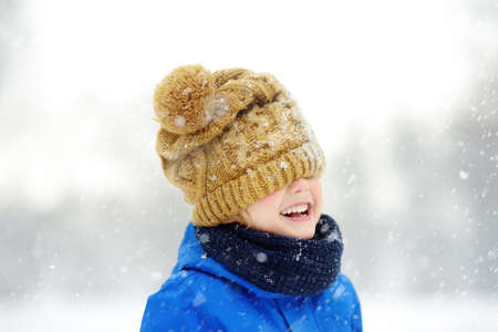 Funny little boy in blue winter clothes walks during a snowfall. Baby having fun while blizzard. Cute child wearing a warm hat low over his eyes. Outdoors winter activities for family with kids. 免版税图像