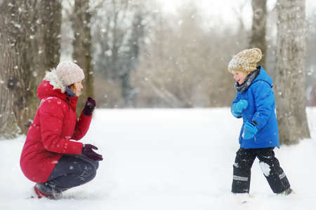 Little boy and his mother having fun playing with fresh snow. Snow fight. People dressed in warm clothes, hat, hand gloves and scarf. Active leisure outdoors for family with child in snowy winter day. 免版税图像