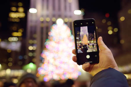 Manhattan, New York, USA - December 25, 2019: Person take shot on smartphone famous huge live Christmas tree near Rockefeller center. Attractions in Christmas NYC. The world's largest holiday tree. 新闻类图片