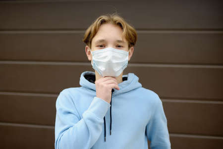 A teenage boy put on a face mask because the second wave of the covid-19 epidemic began. Lockdown again. The mask is the new standard for protection and prevention during a coronavirus or flu outbreak 免版税图像