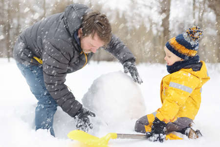 Little boy with his father building snowman in snowy park. Active outdoors leisure with children in winter. Kid during stroll in a snowy winter park 免版税图像