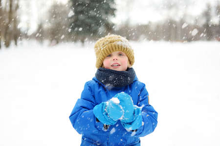 Little boy having fun playing with fresh snow during snowfall. Snowball fight. Kid dressed in warm clothes, hat, hand gloves and scarf. Active leisure outdoors for child on nature in snowy winter day. 免版税图像