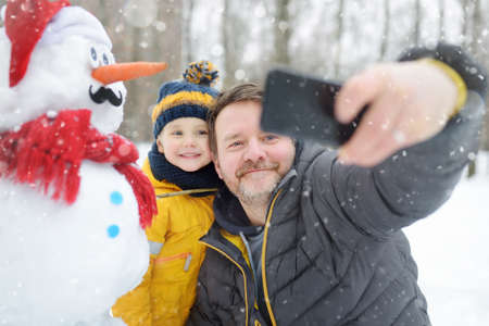 Little boy and his father taking selfie on background of snowman in snowy park. Active outdoors leisure with children in winter. Kid during stroll in a snowy winter park
