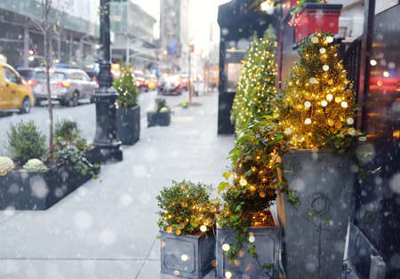 Stylish Christmas decorations - fir tree with garland lights on the street of New York, USA. Festive street decor and illumination on snowy winter day during New Year holiday