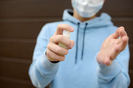 Teenage boy in face mask using sanitizer because the second wave of the covid-19 epidemic began. Lockdown. Mask and disinfection of hands is new normal for protection and prevention during coronavirus
