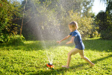 Funny little boy playing with garden sprinkler in sunny backyard. Preschooler child laughing, jumping and having fun with spray of water. Summer outdoors activity for kids.
