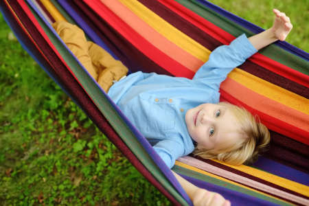 Cute little blond caucasian boy relaxing and having fun in multicolored hammock in backyard or outdoor playground. Summer active leisure for kids. Child swinging on hammock. Activities for children