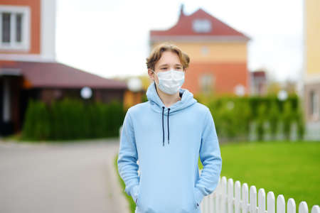 Teenage boy put on face mask because the second wave of covid-19 epidemic began. Lockdown again. Mask is new standard for protection and prevention during a coronavirus or flu outbreak 免版税图像