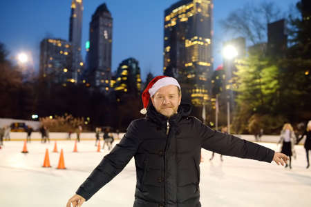 Handsome man in Santa Claus hat skating on rink Central Park on Christmas Eve. Person learns to skate. Sports training for adult. Local and tourists having fun in New York Central Park on winter