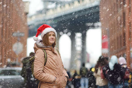 A young woman tourist in a Santa Claus hat walks during a snowfall in New York on Christmas Eve. Manhattan Bridge and skyscrapers of NY on snowy day. Winter holidays in NYC. Snow is rare in New York.