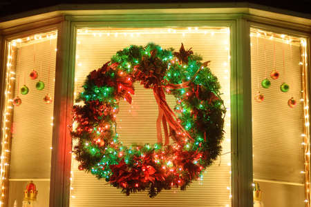 Christmas green wreath with ribbon on the window. Facade to the house decorated for the winter holiday. The typical decoration of the American home for Xmas and New Year.