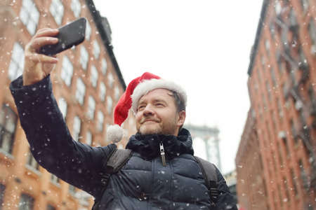 Middle aged man tourist in Santa Claus hat takes selfie on street near the Manhattan Bridge in New York City on Christmas Eve. Winter holidays in NYC. New Year vacations in NYC.