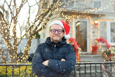 Mature man wearing Santa hat stand near his decorated home. Happy owner decorated his house and yard with garlands for Christmas and New Year. 免版税图像