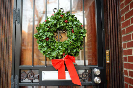 Christmas green wreath with red ribbon on the front door. Entrance to the house decorated for the winter holiday. The typical decoration of the American home for Xmas and New Year.