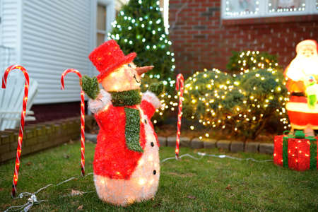Magically decorated courtyard and house for the Christmas and New Year holidays. Glowing the figure of the snowman twinkle beautifully. Typical street decoration for winter holidays in the USA.