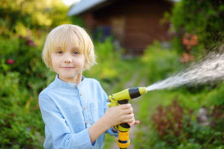 Funny little boy watering plants and playing with garden hose with sprinkler in sunny backyard. Preschooler child having fun with spray of water. Summer outdoors activity for kids. 免版税图像